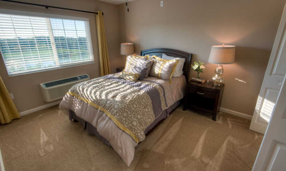 Resident bedroom with large windows at Inspired Living at Lakewood Ranch in Bradenton, Florida