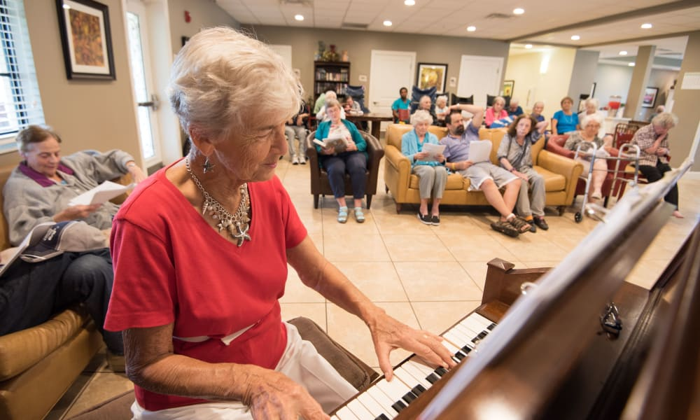Resident playing the piano at Inspired Living Royal Palm Beach in Royal Palm Beach, Florida.