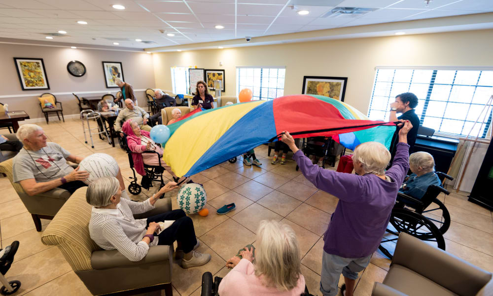 Residents playing a wellness game at Inspired Living at Royal Palm Beach in Royal Palm Beach, Florida
