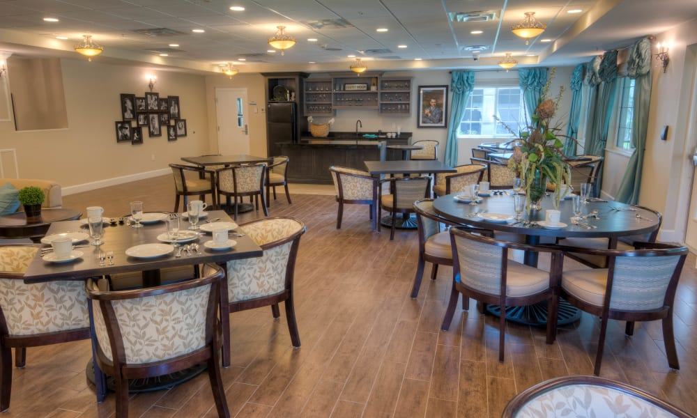 Open dining hall with hardwood floors at Inspired Living Tampa in Tampa, Florida