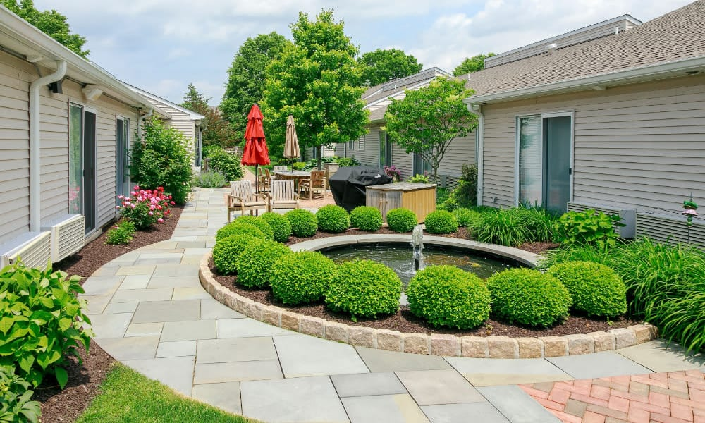 A fountain surrounded by shrubs at Traditions of Lansdale in Lansdale, Pennsylvania