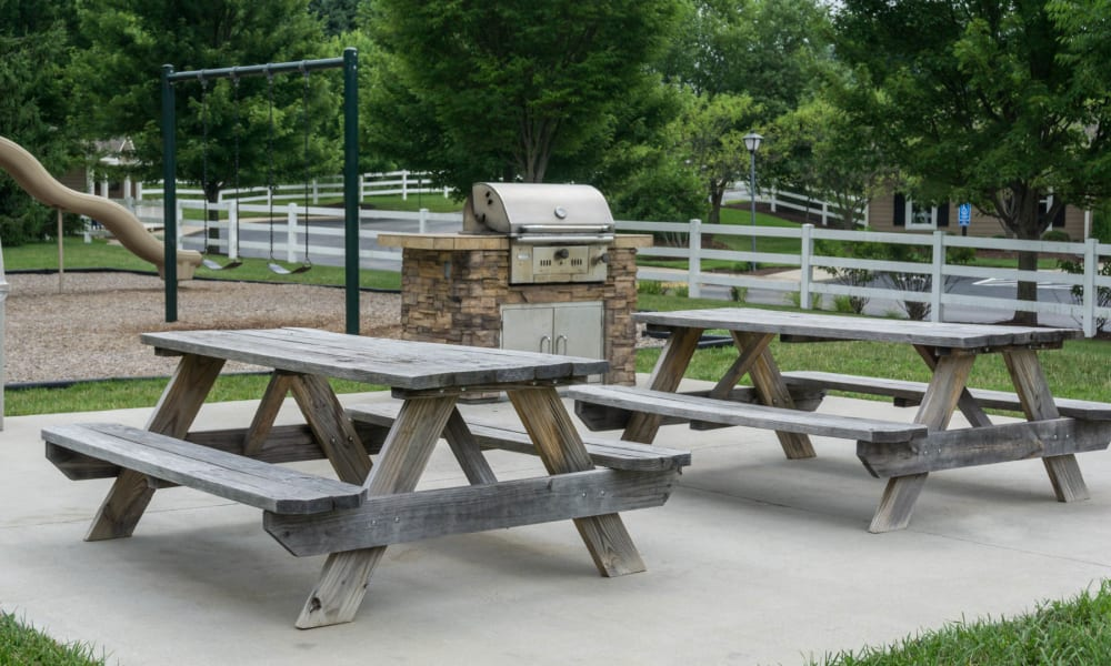 A few picnic benches by a grill at Paddock Club Apartments in Florence, Kentucky