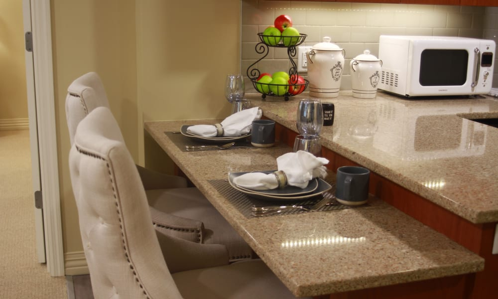 A kitchen with bar top seating at Anthology of Olathe in Olathe, Kansas