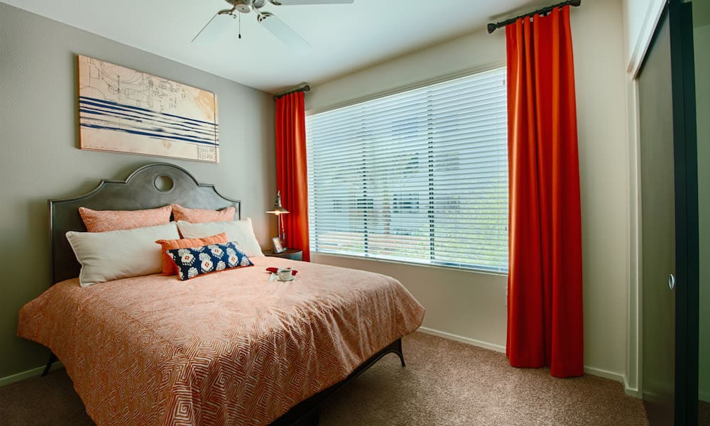 Guest bedroom with draped windows and a ceiling fan in a model home at Cactus Forty-2 in Phoenix, Arizona
