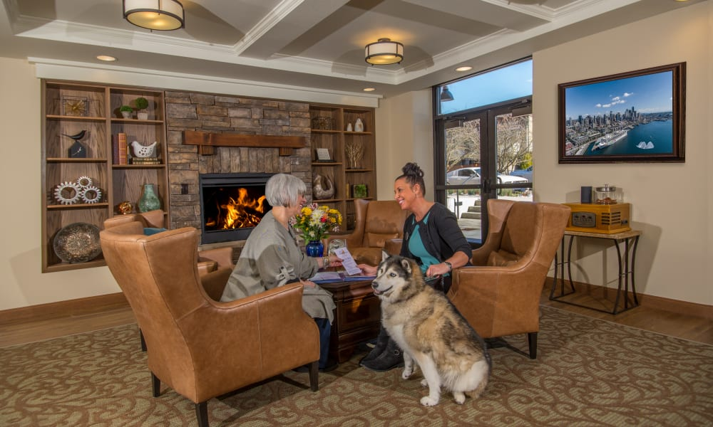 Resident talking to a caretaker with a dog at Quail Park Memory Care Residences of West Seattle in Seattle, Washington