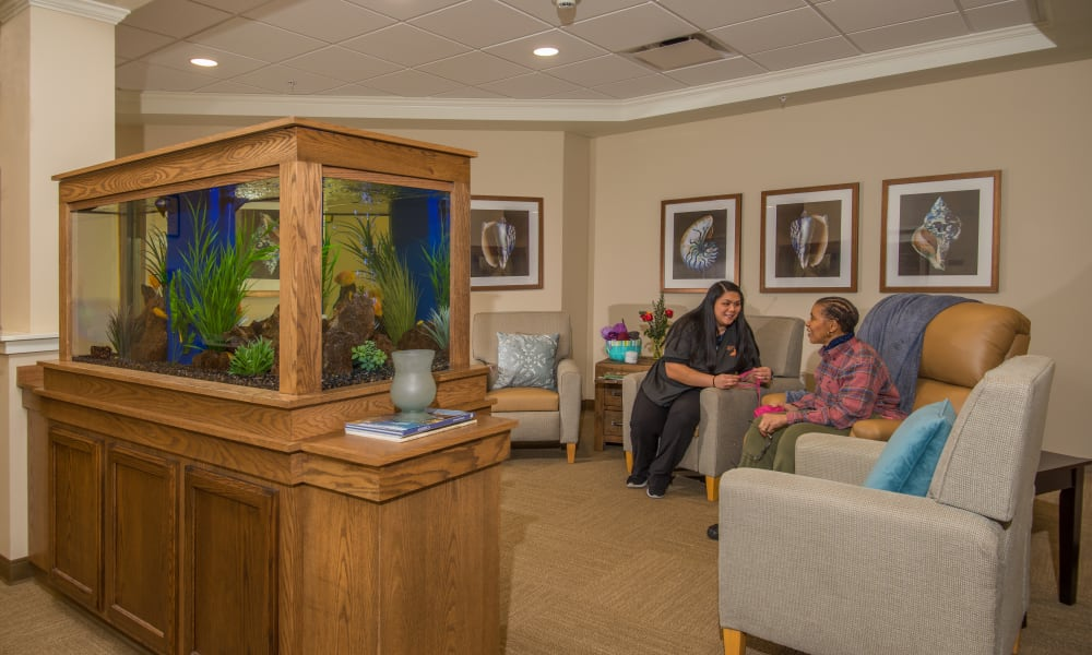 Resident talking to a caretaker in lounge area at Quail Park Memory Care Residences of West Seattle in Seattle, Washington