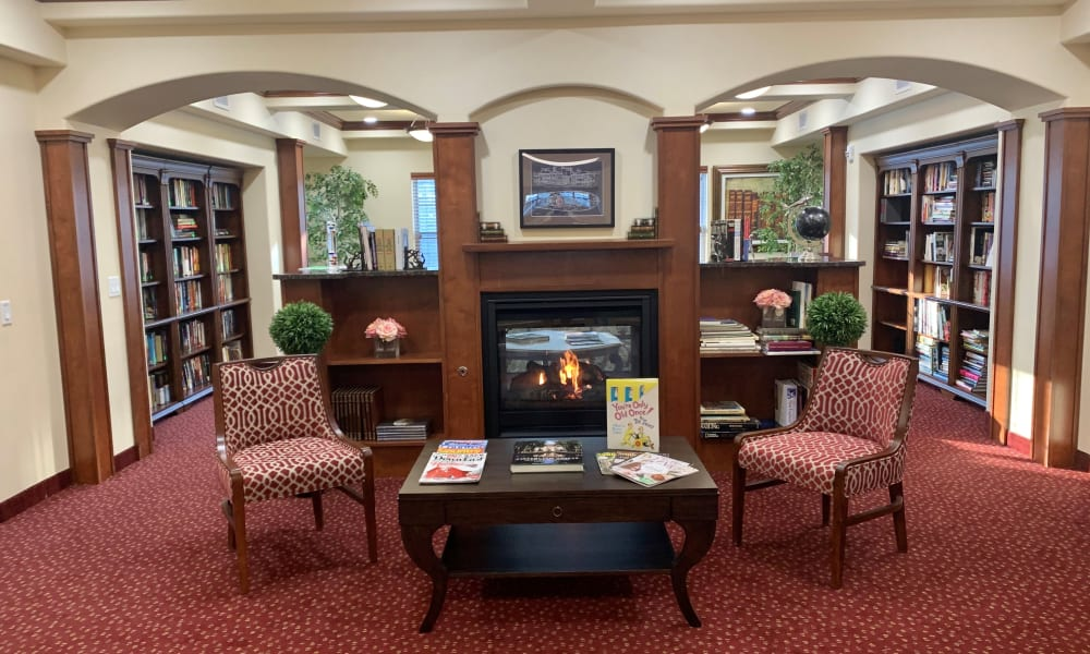 Gorgeously decorated library with seating in front of the fireplace at Ashton Gardens Gracious Retirement Living in Portland, Maine