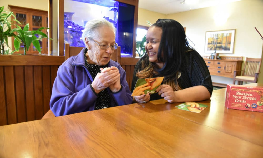 Caretaker working on a memory game with a resident at Quail Park Memory Care Residences of Visalia in Visalia, California