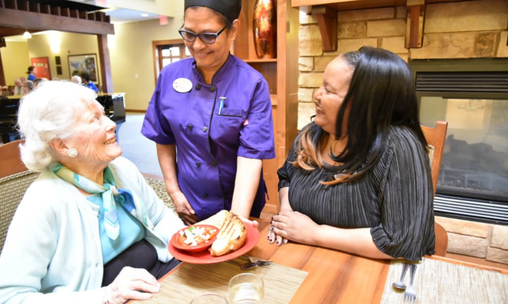Resident being served a meal at Quail Park Memory Care Residences of Visalia in Visalia, California
