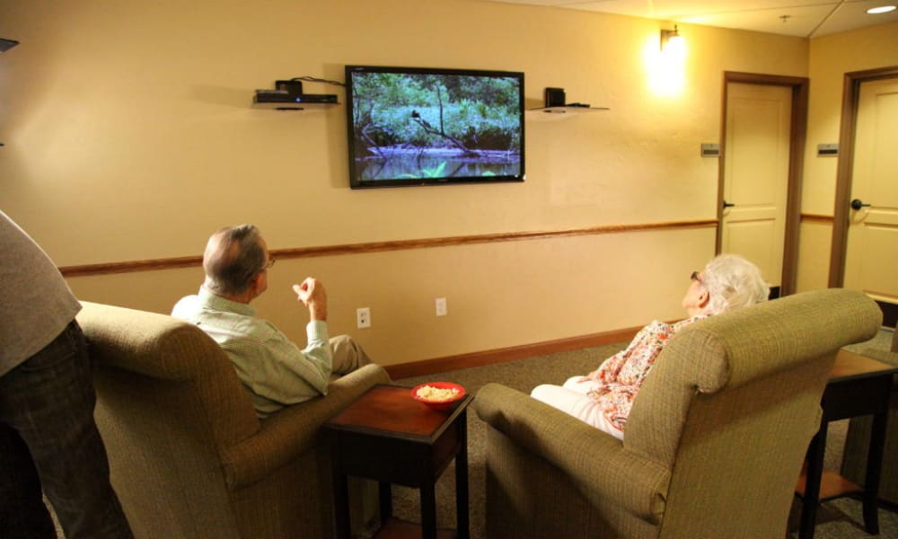 Two residents sitting and watching tv at Quail Park Memory Care Residences of Visalia in Visalia, California