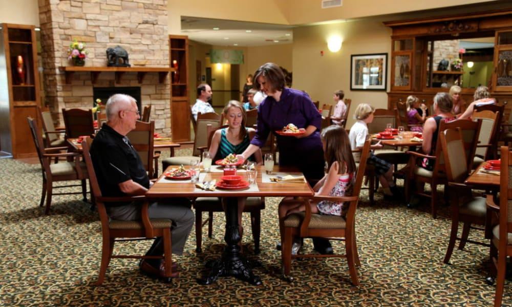 Dining room full of residents having lunch at Quail Park Memory Care Residences of Visalia in Visalia, California