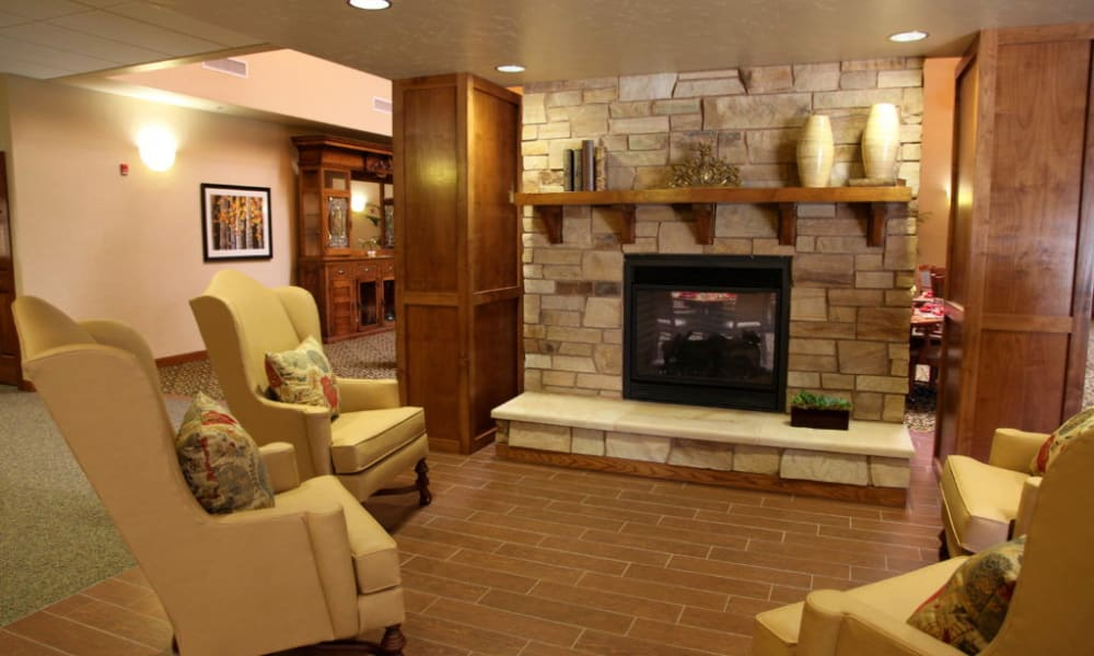 Lounge with a fireplace and ample seating at Quail Park Memory Care Residences of Visalia in Visalia, California
