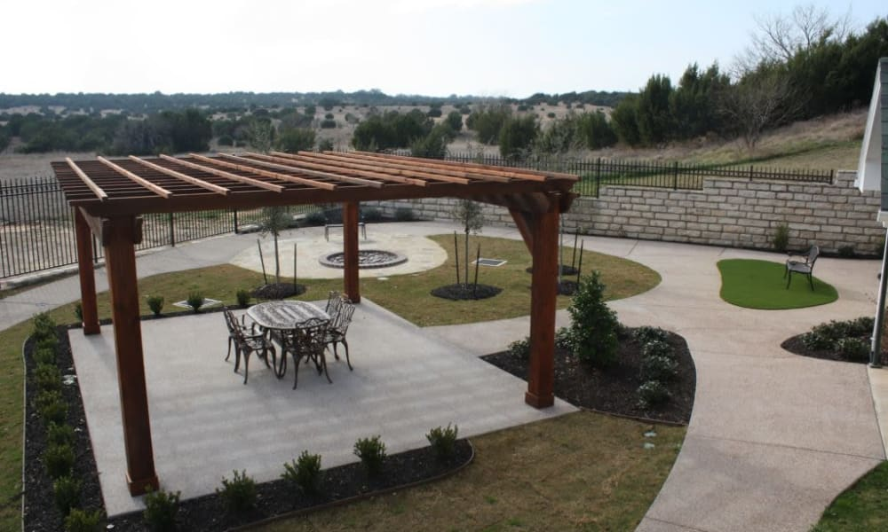 Community courtyard with paved walkways and a covered patio at Quail Park of Granbury in Granbury, Texas