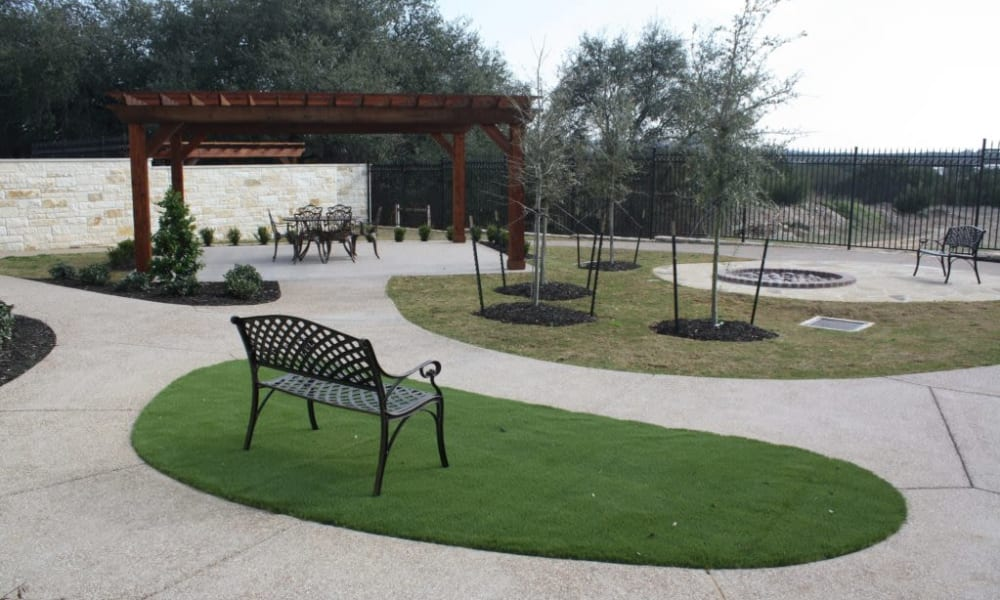 A bench on a patch of grass at Quail Park of Granbury in Granbury, Texas