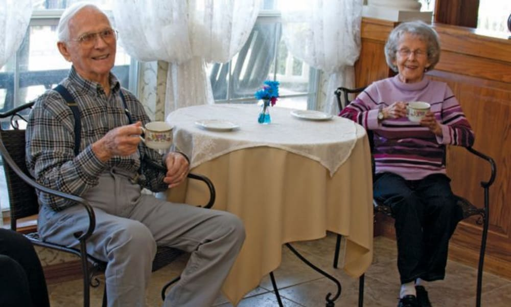 Resident couple sitting and drinking tea at Quail Park of Granbury in Granbury, Texas