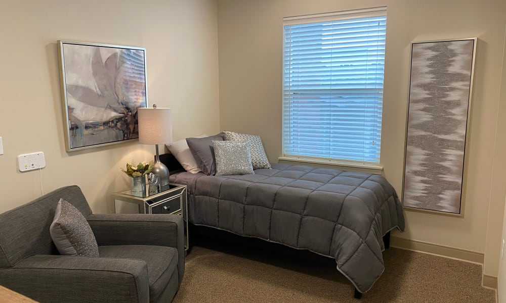 Studio senior apartment with grey linen at Quail Park Memory Care Residences of West Seattle in Seattle, Washington