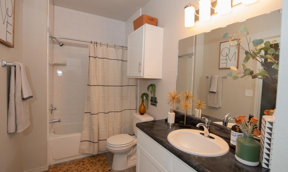 Bright bathroom with shower and tub combo at Cedar Ridge in Tulsa, Oklahoma
