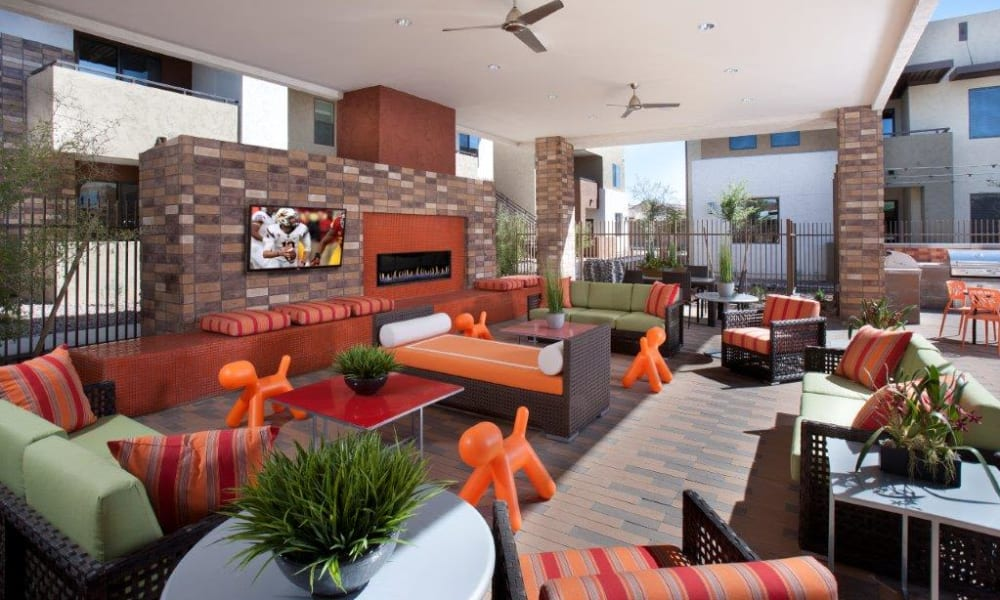 Flatscreen TV and a fireplace at a covered outdoor lounge area at Vive in Chandler, Arizona