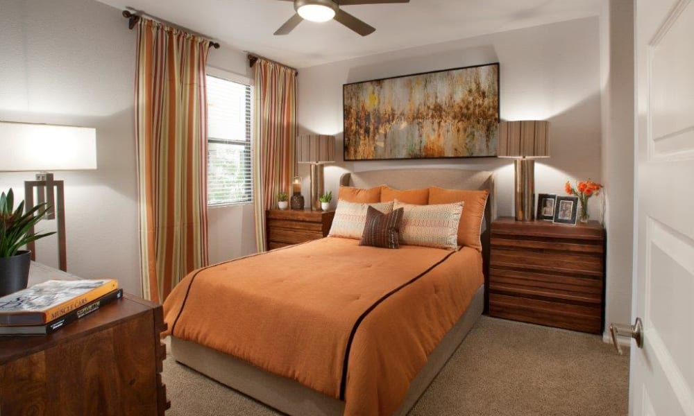 Well-furnished master bedroom with draped windows in a model apartment at Vive in Chandler, Arizona