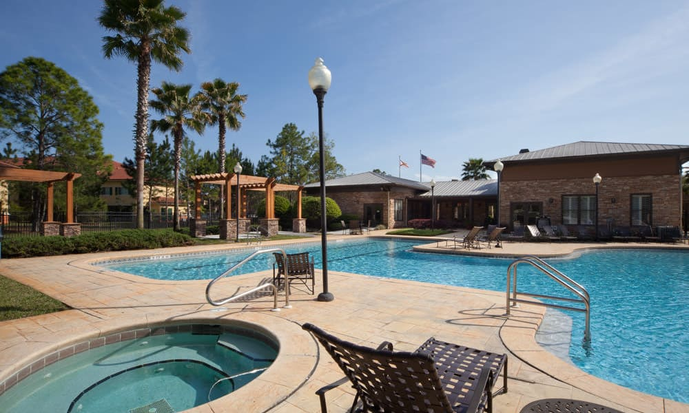 Spa and swimming pool area with palm trees nearby at Wimberly at Deerwood in Jacksonville, Florida