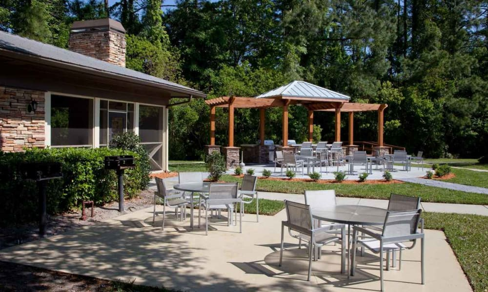 Tables and chairs shaded by mature trees at one of the outdoor common areas at Wimberly at Deerwood in Jacksonville, Florida