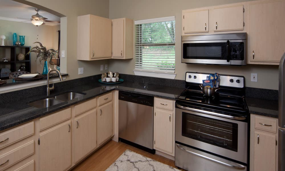 Stainless-steel appliances and an expansive granite countertop in a model home at Wimberly at Deerwood in Jacksonville, Florida