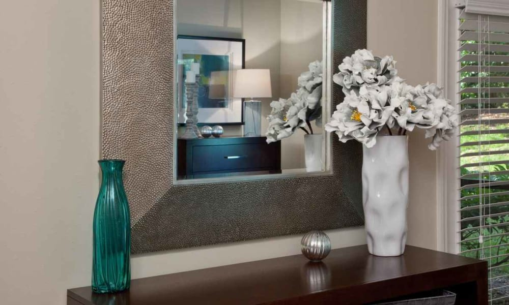 Decorative mirror above vases on an end table in a model home at Wimberly at Deerwood in Jacksonville, Florida
