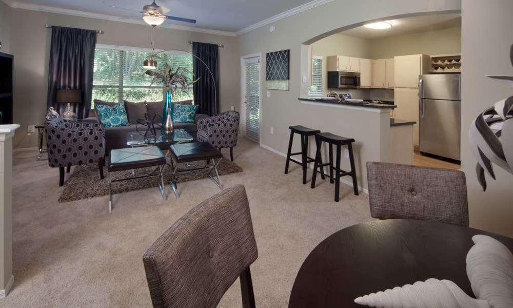 Well-furnished living area with draped windows in a model home at Wimberly at Deerwood in Jacksonville, Florida