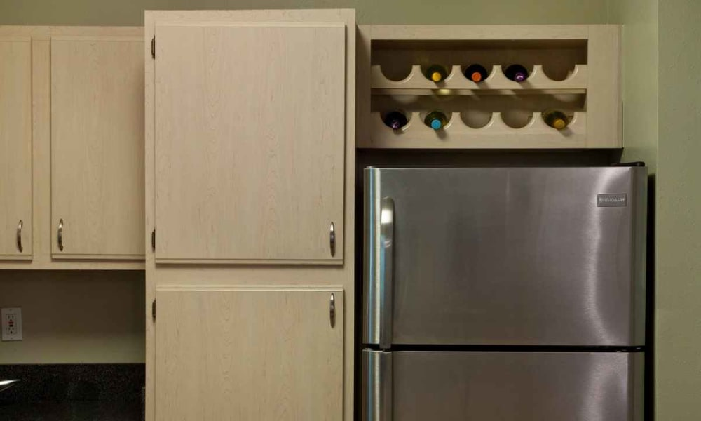 Built-in wine rack above the stainless-steel refrigerator in a model apartment at Wimberly at Deerwood in Jacksonville, Florida