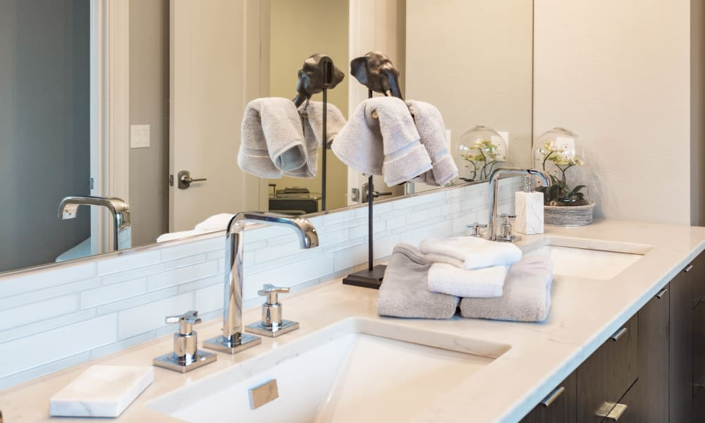 Dual sinks in the master bathroom of a model home at Olympus Court Apartments in Bakersfield, California