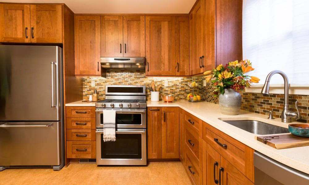 Cherry wood cabinetry in a model home's kitchen at Olympus Court Apartments in Bakersfield, California