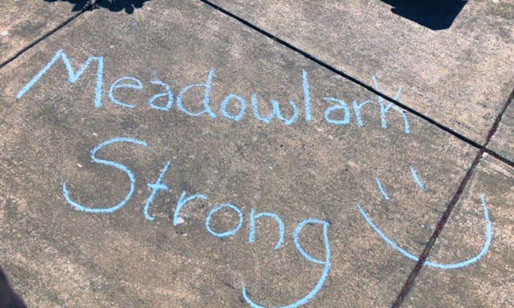 Meadowlark Strong written in sidewalk chalk