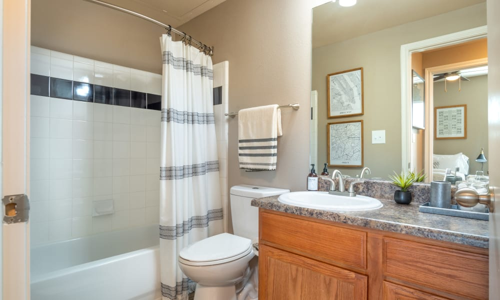 Bathroom with large vanity mirror and shower bathtub at Olympus Team Ranch in Benbrook, Texas