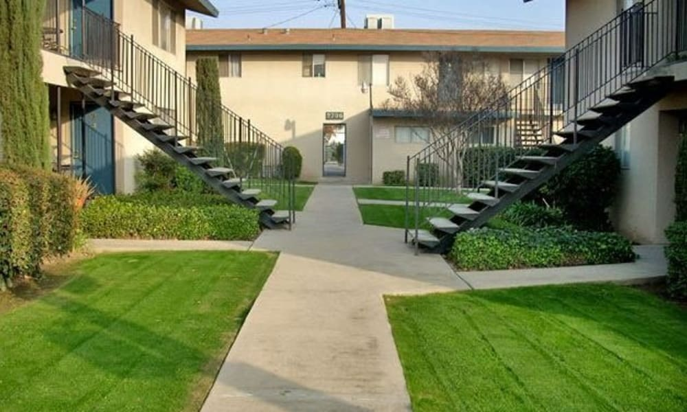 Well manicured exterior landscape with stairwells at Highland View Court in Bakersfield, California