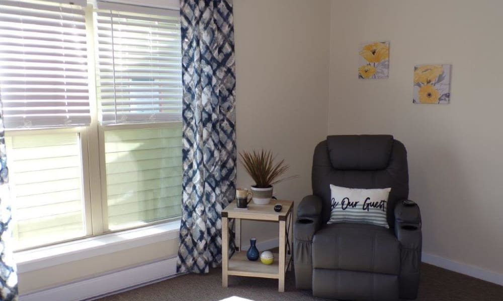 Comfortable chair by window in Recovery Care Living Room at Landings of Oregon in Oregon, Ohio