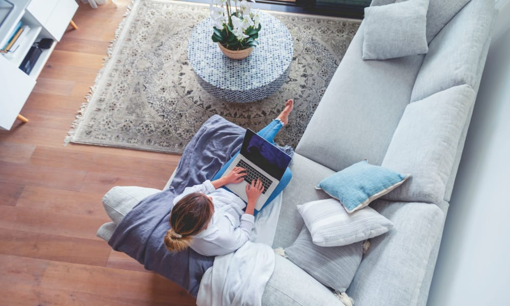 Resident working on her laptop while relaxing on the couch in the living room at Lehigh Valley in Whitehall, Pennsylvania