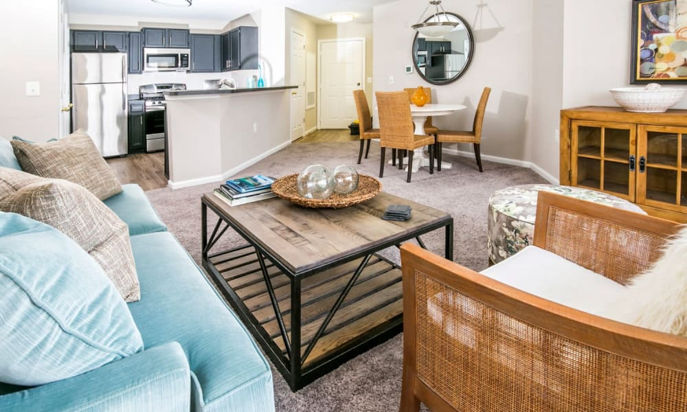 Comfortably furnished living area in a model home's open-concept floor plan at Arbor Ridge Apartments in Owings Mills, Maryland