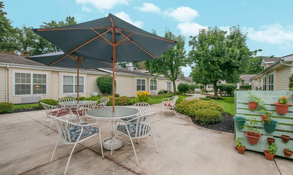 Patio table with umbrella and landscaped yard at Randall Residence of Newark in Newark, Ohio