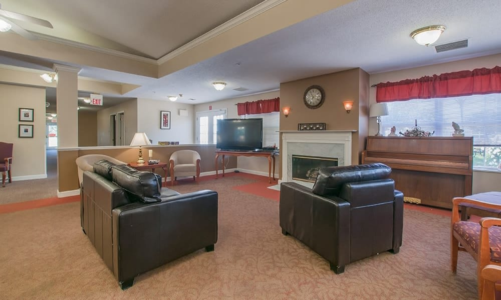 Resident living area with leather couches at Randall Residence of Troy in Troy, Ohio