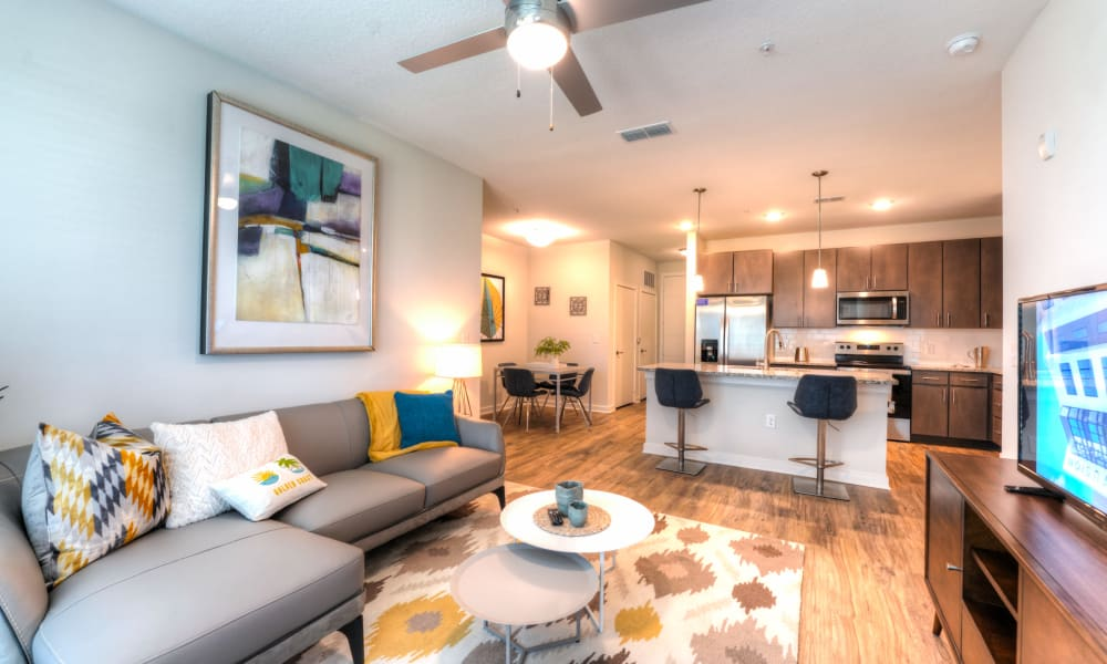 Spacious living room and kitchen featuring breakfast bar seating at Fusion apartments in Jacksonville, Florida