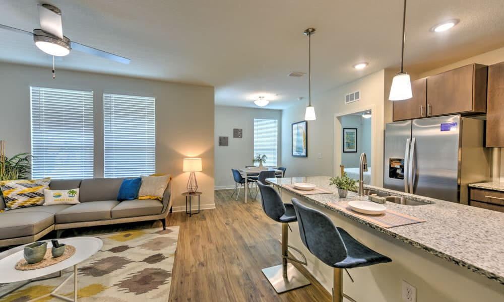 Spacious living room and a kitchen featuring breakfast bar seating at Fusion apartments in Jacksonville, Florida