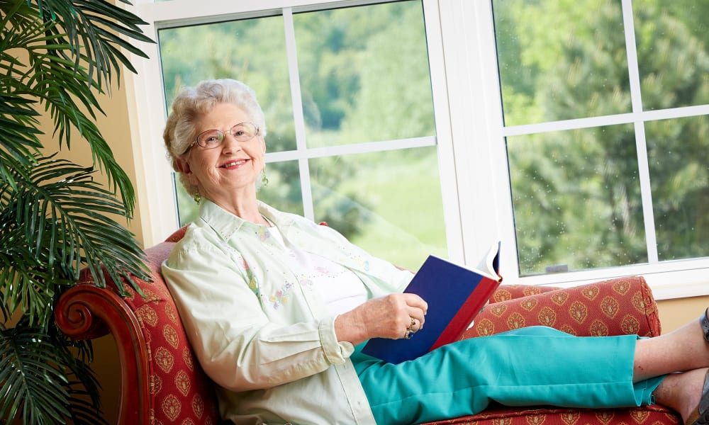 Resident laying by a sunlit windowsill reading a book at Deer Crest Senior Living in Red Wing, Minnesota