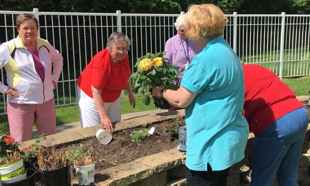Group of active residents plating flowers outside at Deer Crest Senior Living in Red Wing, Minnesota