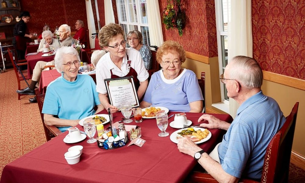Residents looking at a menu in the dining hall at Deer Crest Senior Living in Red Wing, Minnesota