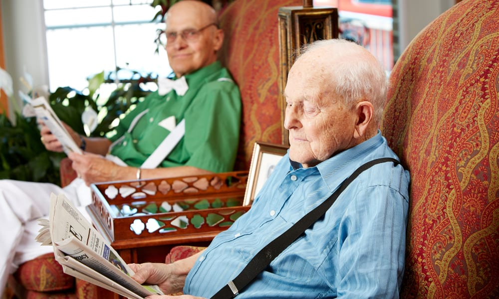 Two residents sitting and reading the newspaper at Deer Crest Senior Living in Red Wing, Minnesota