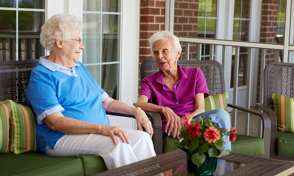 Two residents sitting on the porch and talking at Deer Crest Senior Living in Red Wing, Minnesota