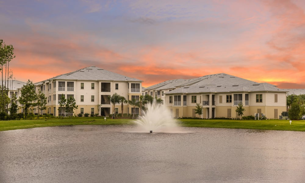 Bright colored clouds at twilight above the onsite pond with a fountain at Palm Bay Club in Jacksonville, Florida