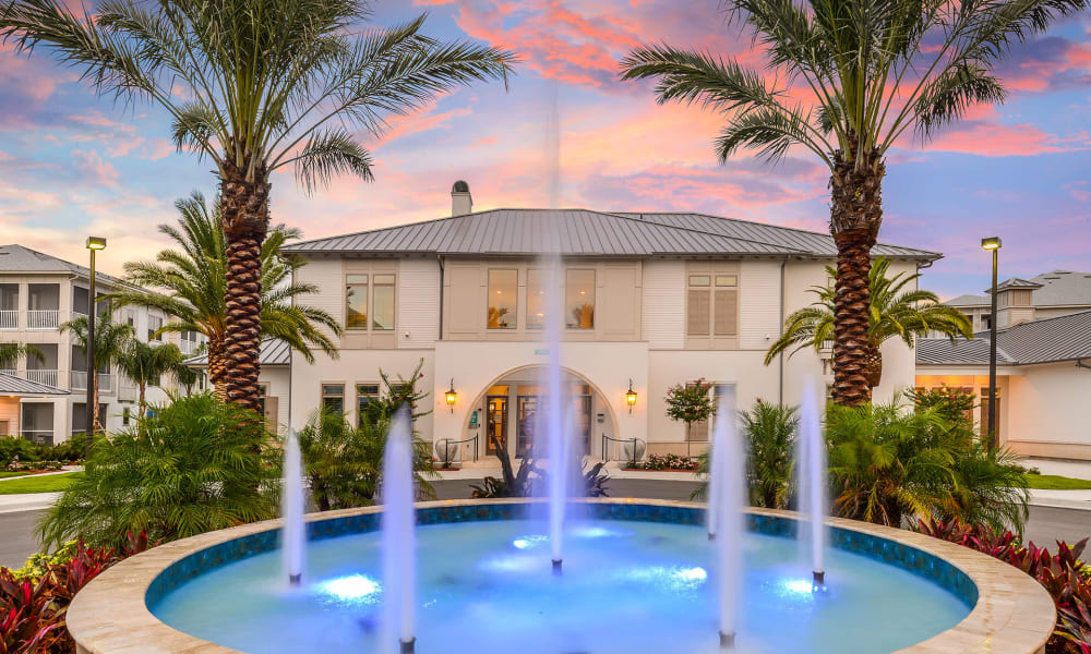Underwater lights illuminating the fountain at the community's entrance at dusk at Palm Bay Club in Jacksonville, Florida