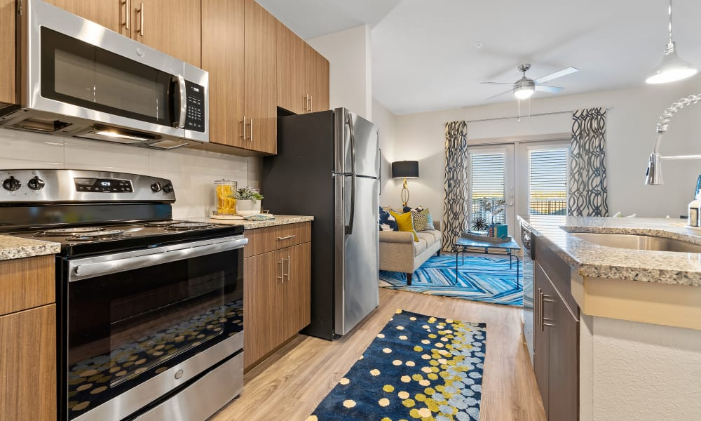 Kitchen with wood-style cabinets at McCarty Commons in San Marcos, Texas