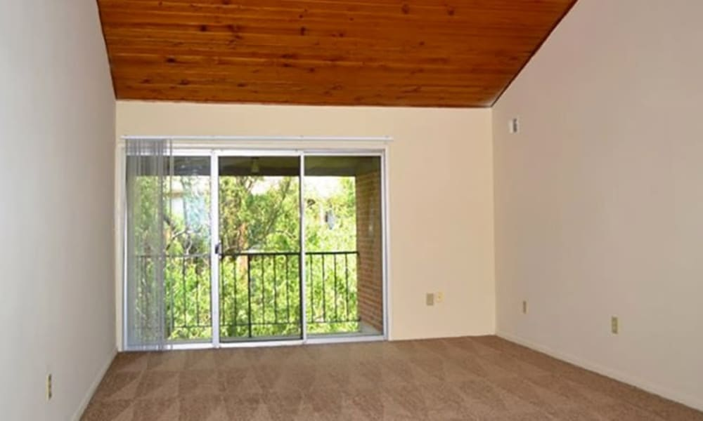 A living room with balcony access at Woodmere Apartments in Cincinnati, Ohio